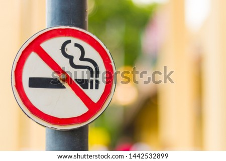 Old No Smoking Label Stick to the pole in the public park with blur nature background