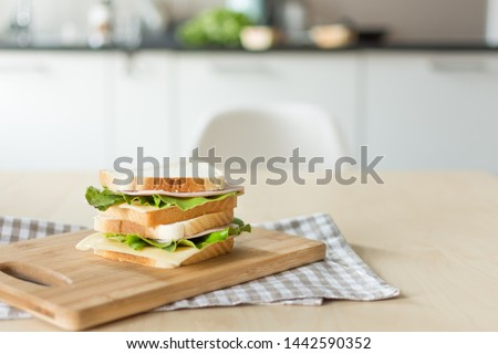 Sandwich with cheese and ham on cutting board on the table in the bright kitchen. Lunch. Sandwich with lettuce. Healthy eating concept. #1442590352