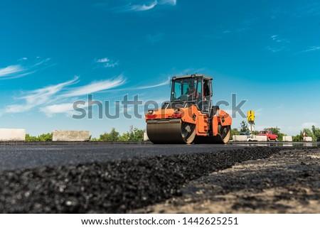 Roller rolling fresh hot asphalt on the new road. Road construction. #1442625251