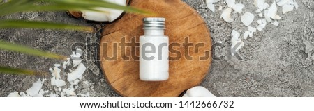 top view of coconut shavings near wooden board with coconut cream on grey textured background, panoramic shot #1442666732