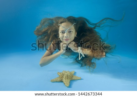 Young beautiful girl lies at the bottom looks at a starfish and smiling on the bottom of the swimming pool. underwater girls pictures