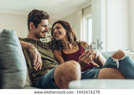Loving couple sitting on sofa at home. Man and woman relaxing on couch with smartphone in living room. Royalty-Free Stock Photo #1442676278