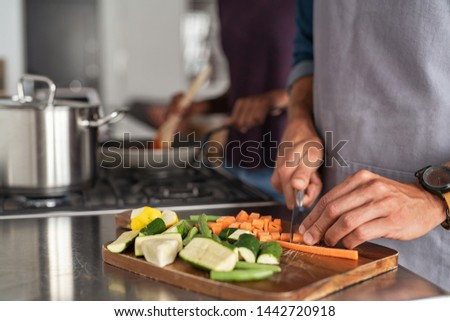 Closeup of hands slicing carrots on chopping board. Closeup of hands cutting vegetables in kitchen near the burners. Detail of man wearing apron chopping vegetables for a recipe at home. #1442720918