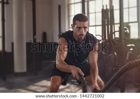 Athletic young man doing some fitness exercises with a rope. Determined fit guy doing battle ropes exercise at the grunge gym. Handsome man training with effort. #1442721002