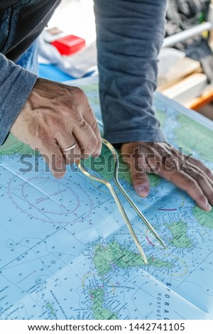 Sailor with divider in front of navigation chart of coastal area. Captain navigating sail boat ship #1442741105