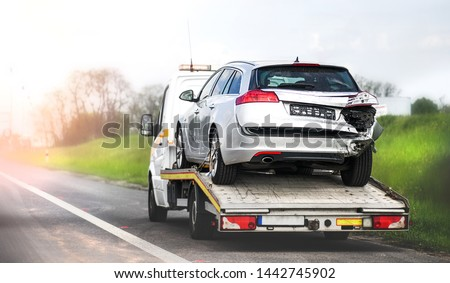 Loading broken car on a tow truck. Damage vehicle after crash accident on the highway road. #1442745902