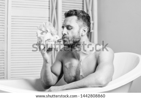 Handsome muscular man relaxing bathtub with yellow duck. Macho with sponge take bath at home. Taking bath with soap suds. Beauty routine. Relax and fun concept. Daily bath helps beat depression. #1442808860
