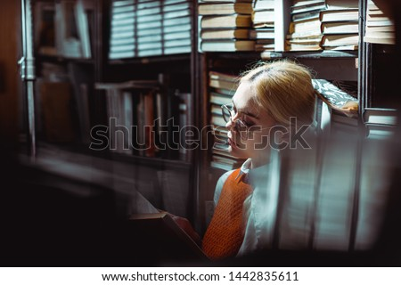 selective focus of beautiful and blonde woman reading book in library  #1442835611