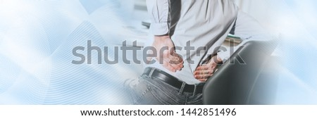 Businessman suffering from back pain in office, light effect; panoramic banner #1442851496