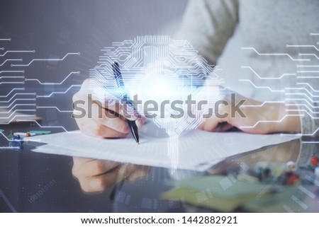 Double exposure of woman's writing hand on background with brain hud. Concept of learning. #1442882921