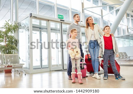 Parents and two children with luggage in the airport terminal are looking forward to a family vacation #1442909180
