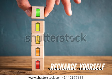 """Hand stacking cubes with icons symbolizing recharging mental engergy and the message """"recharge yourself"""" Royalty-Free Stock Photo #1442977685"""