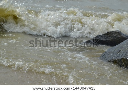 Small sea waves, on the stones, with sea foam, on a summer day #1443049415