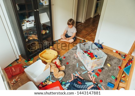 Indoor portrait of a child playing in a very messy room, throwing teddy bear on the floor #1443147881