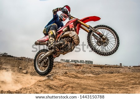 Shot of the professional motocross rider on his motorcycle on the extreme terrain track. Biker flying on a motocross motorcycle. Construction background and sky. #1443150788