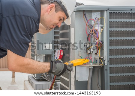 Professional hvac technician measuring amperage on an air conditioner unit #1443163193