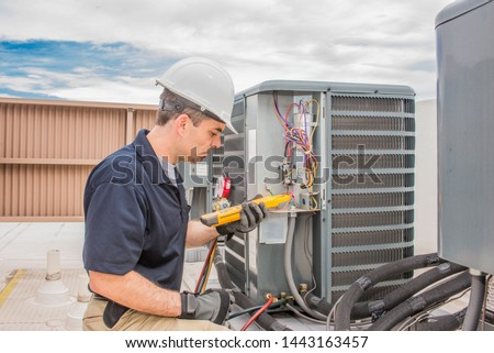Trained hvac technician holding a voltage meter, performing preventative maintenance on a air conditioning condenser unit. #1443163457