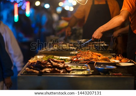 Stock image of chef cook the bbq seafood on beach for dinner part, roasted seafood party, grilled lobster cook on charcoal stove. Grilled king prawns, squid on bbq fire. Thai street food night market #1443207131