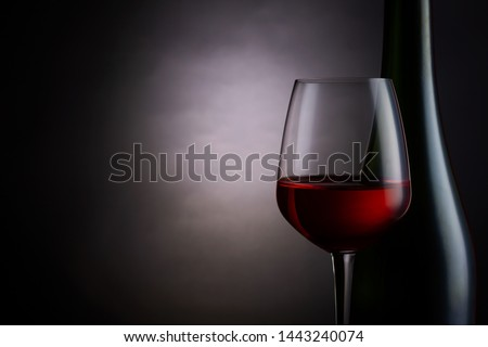Red wine in a glass with wine bottle on dark background. #1443240074
