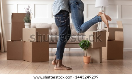 Close up young husband in jeans lift wife surrounded by cardboard boxes excited to move in new flat, happy african American couple have fun hug feel euphoric relocating together to own house Royalty-Free Stock Photo #1443249299