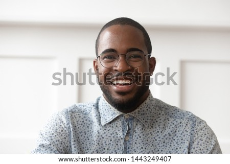 Headshot portrait of smiling african American male in glasses looking at camera talking or shooting, happy black man wear spectacles posing laugh with white toothy smile, recording video on gadget #1443249407