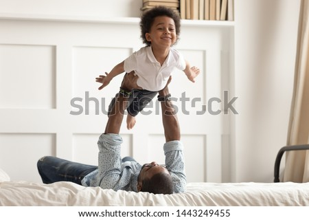 Loving african American dad lying on bed playing with cute little toddler son acting plane, happy black father have fun engaged in funny activity with small kid hold lift in arms in bedroom