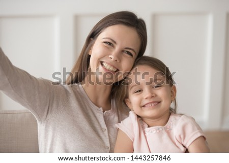 Head shot portrait of smiling mother with daughter taking selfie for social networks at home, looking at camera, happy mum hugging adorable preschool child, posing for family photo together #1443257846