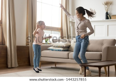 Happy mother and preschool daughter jumping, having fun at home, older sister with preschool girl dancing to favorite song, enjoying music, funny activity, enjoying family weekend together #1443257855