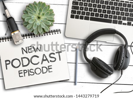 top view of text NEW PODCAST EPISODE on notepad with laptop computer, potted plant and recording microphone on white wooden table, podcasting concept