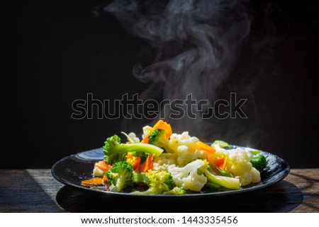 The steam from the vegetables carrot broccoli Cauliflower in a black plate  , a steaming. Boiled hot Healthy food on table on black background,hot food and healthy meal concept #1443335456