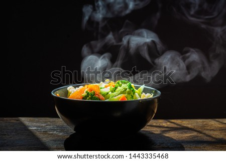 The steam from the vegetables carrot broccoli Cauliflower in black bowl  , a steaming. Boiled hot Healthy food on table on black background,hot food and healthy meal concept #1443335468