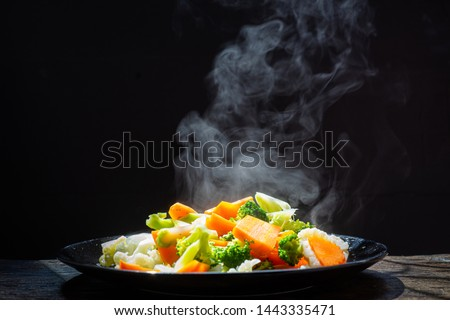 The steam from the vegetables Carrot Broccoli Cauliflower in a black plate  , a steaming. Boiled hot Healthy food on table on black background,hot food and healthy meal concept #1443335471