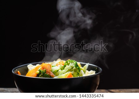 The steam from the vegetables carrot broccoli Cauliflower in black bowl  , a steaming. Boiled hot Healthy food on table on black background,hot food and healthy meal concept #1443335474
