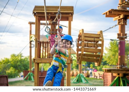 Little cute boy enjoying activity in a climbing adventure park on a summer sunny day. toddler climbing in a rope playground structure. Safe Climbing extreme sport with helmet and Carabiner. insurance #1443371669