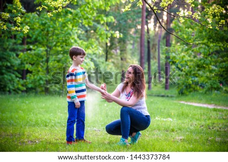 Young woman mother applying insect repellent to her son before forest hike beautiful summer day or evening. Protecting children from biting insects at summer. Active leisure with kids #1443373784