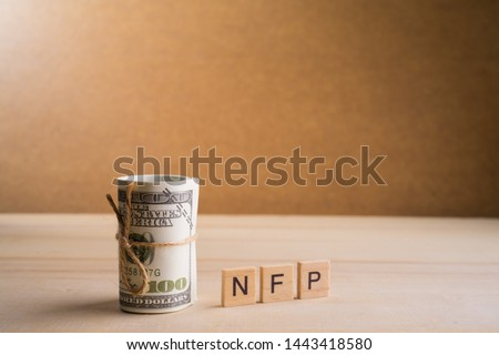 Non-farm payrolls (NFP) Conceptual image with a roll of 100 American Dollar USD on wooden base #1443418580