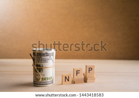 Non-farm payrolls (NFP) Conceptual image with a roll of 100 American Dollar USD on wooden base #1443418583