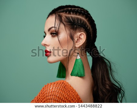 Brunette girl with perfect makeup. Beautiful model woman with curly hairstyle. Care and beauty hair products. Lady with braided hair. Model with jewelry. Turquoise background #1443488822