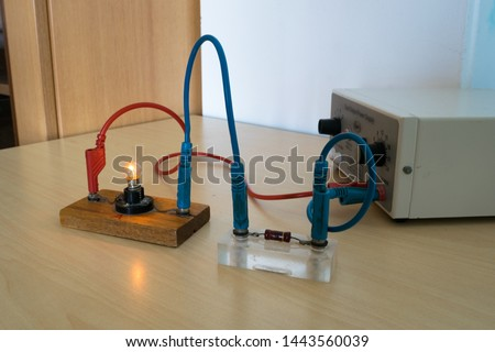 Electrical experiment in physics laboratory. Electrical circuit with resistor and light bulb. #1443560039