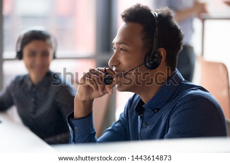 Smiling young african businessman call center agent wear wireless headset laugh at workplace, cheerful happy black male telemarketer operator have fun at work break in customer service support office #1443614873