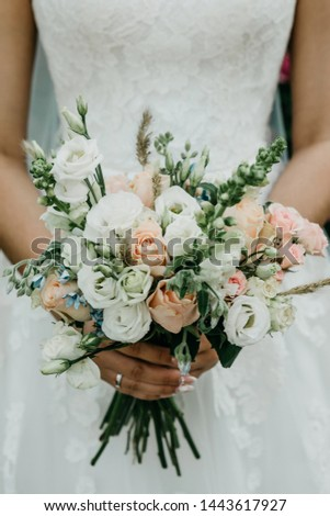 A bride in a white dress is holding a beautiful wedding bouquet of white and pink roses. Wedding celebration. #1443617927