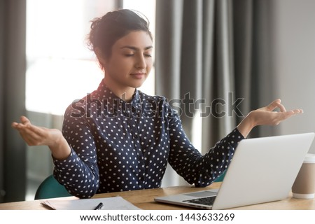 Mindful calm indian young business woman meditate at work desk with eyes closed, healthy hindu girl take break relax in office doing yoga at workplace feel balance no stress and peace of mind concept #1443633269