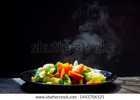 The steam from the vegetables carrot broccoli Cauliflower in a black plate  , a steaming. Boiled hot Healthy food on table on black background,hot food and healthy meal concept #1443706121