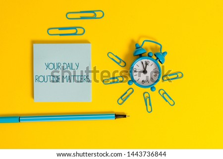 Word writing text Your Daily Routine Matters. Business concept for practice of regularly doing things in fixed order Metal alarm clock wakeup clips ballpoint notepad colored background. #1443736844