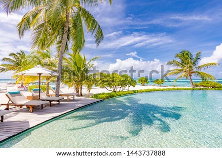 Beautiful luxury umbrella and chair around outdoor swimming pool in hotel and resort with coconut palm tree on blue sky. Luxurious summer vacation and holiday banner. Boost up color Processing #1443737888