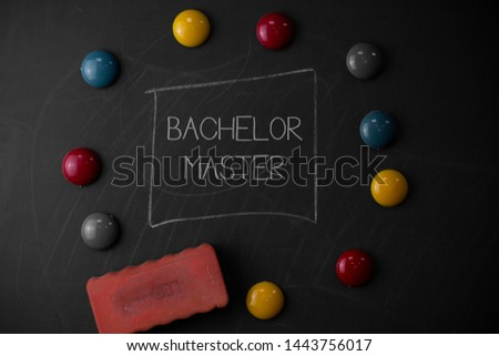 Text sign showing Bachelor Master. Conceptual photo An advanced degree completed after bachelor s is degree Round Flat shape stones with one eraser stick to old chalk black board. #1443756017