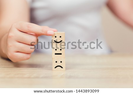 customer pressing smiley face emoticon on wood cube, Service rating, satisfaction concept. #1443893099