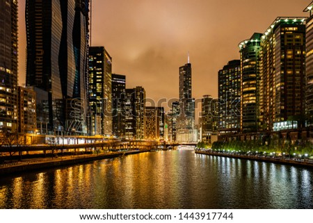 Chicago city cityscape, sunset time. Chicago city illuminated skyscrapers at night. Reflections on the river canal