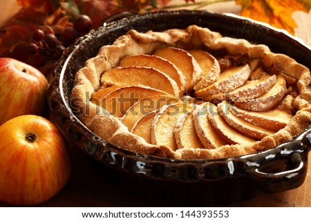 Arrangement of home-made apple pie and apples. Royalty-Free Stock Photo #144393553