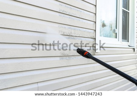 Cleaning service washing building facade with pressure water. Cleaning dirty wall with high pressure water jet. Power washing the wall. Cleaning the facade of the house. Before and after washing #1443947243